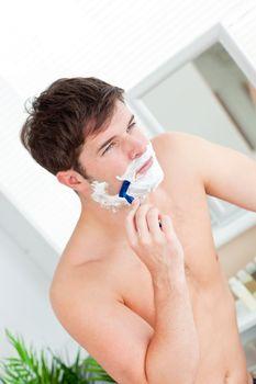 Attractive caucasian man shaving in the bathroom