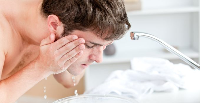 Young caucasian man spraying water on his face after shaving in