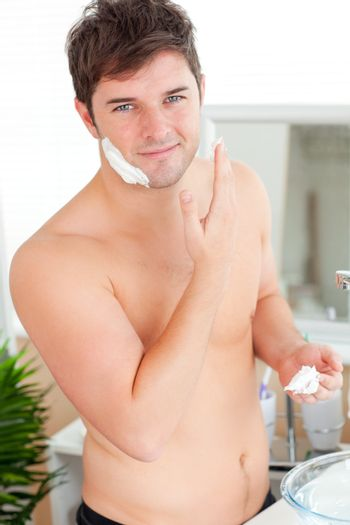Attractive caucasian man ready to shave in the bathroom