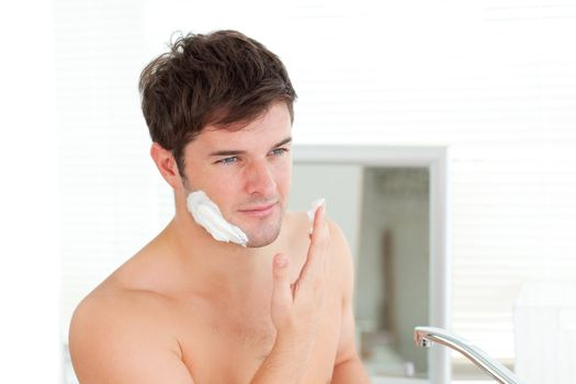 Handsome caucasian man ready to shave in the bathroom
