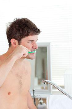 Good-looking young man brushing his teeth in the bathroom