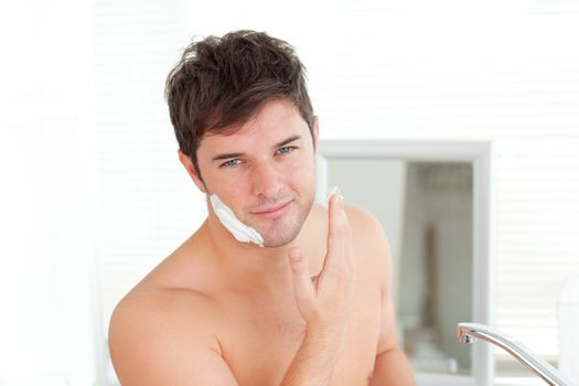 Cute caucasian man ready to shave in the bathroom