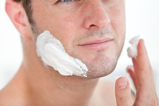 Close-up of a cute man preparing to shave in the bathroom