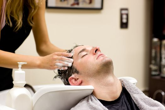 Attractive man having a shampoo