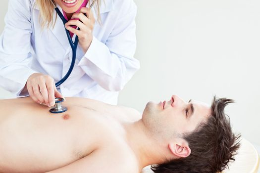 Close-up of a doctor feeling the breathing of a patient lying on