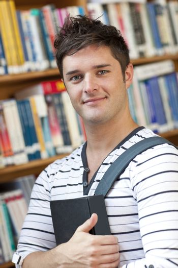 Portrait of a smart student holding a book standing in the libra