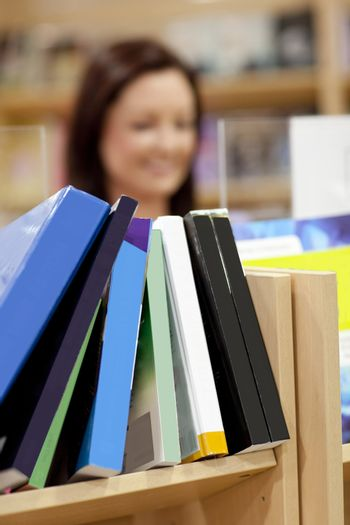 Close-up of a book shelf in a library with female customer in th