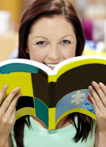 Portrait of a beautiful woman holding a book in a library smilin