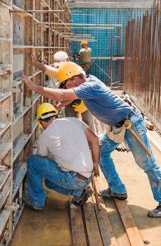 Construction builders positioning concrete formwork frames