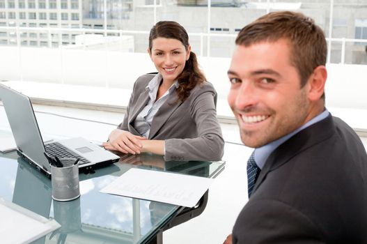 Happy businesspeople working together on a laptop during a meeti