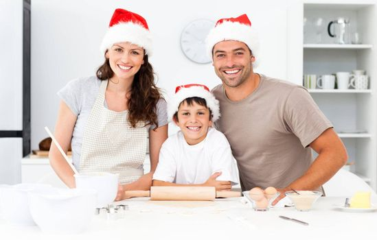Portrait of a happy family preparing christmas cookies in the kitchen