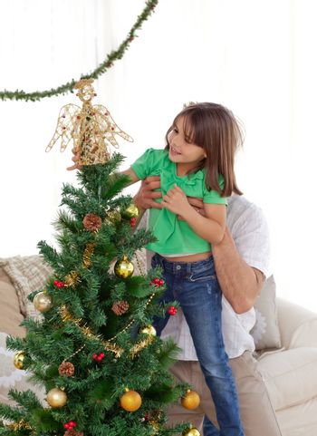 Attentive father holding her daughter to decorate the christmas
