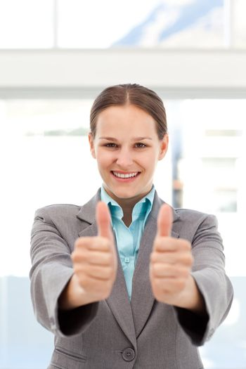 Proud businesswoman doing thumbs up