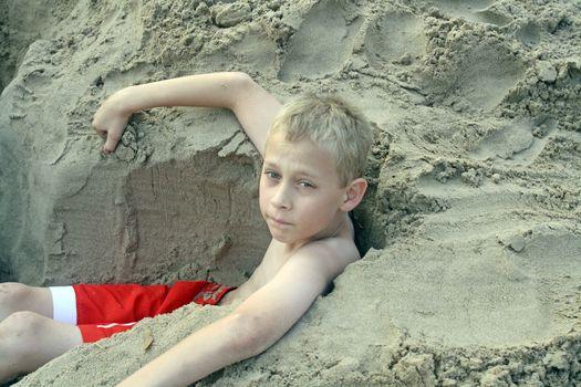teenage boy playing in sand