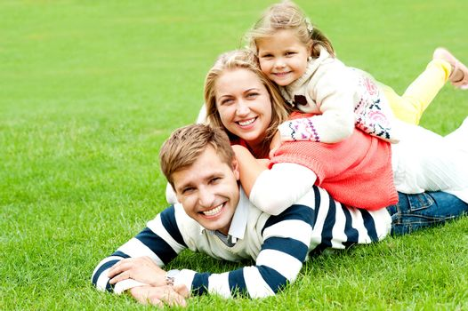 Husband, wife and child piled on each other