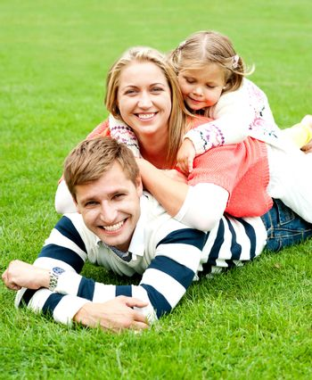 Young mother sandwiched between her daughter and husband