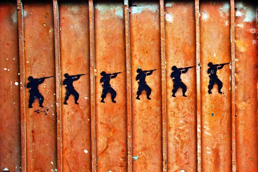 Graffiti of soldiers with guns on an old metal door.