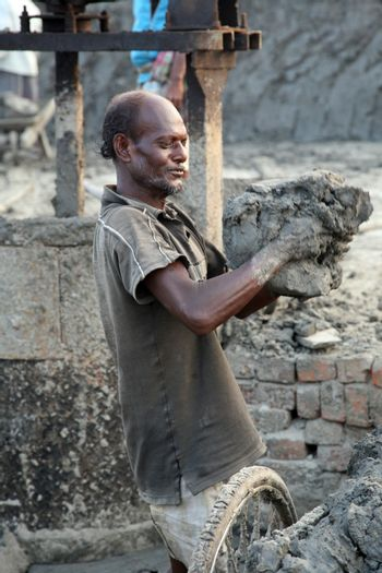 SARBERIA,INDIA, JANUARY 14: Brick field. Laborers are carrying deposited soil for making raw brick. on January 14, 2009 in Sarberia, West Bengal, India.