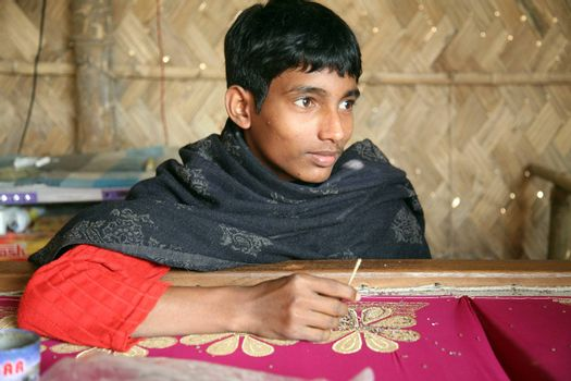 KUMROKHALI, INDIA - JAN 16: Anandalok Naskar, 15,  working on the decoration of textiles in Kumrokhali, India on Jan 16, 2009.According to the statistics there are 20 million child laborers in the country
