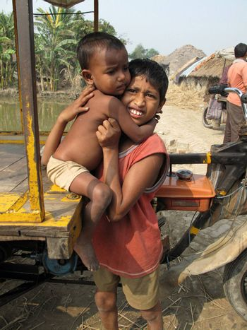 SUNDARBANDS, WEST BENGAL, INDIA - JANUARY 18: Sayan Payne, 12, holding his little brother Rajneesh, 3, at remote village in Sundarbands, West Bengal, India on January 18, 2009.