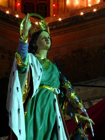 A papier mache statue of Saint Catherine being part of various street decorations for the feast of Saint Catherine in Zejtun, Malta.