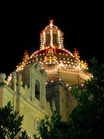 The dome of a church in Zejtun in Malta brightly lit for the feast of Saint Catherine.