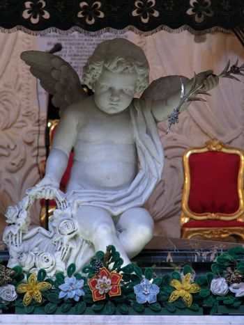 A marble statue of an angel in a church in Valletta carrying a basket full of flowers.