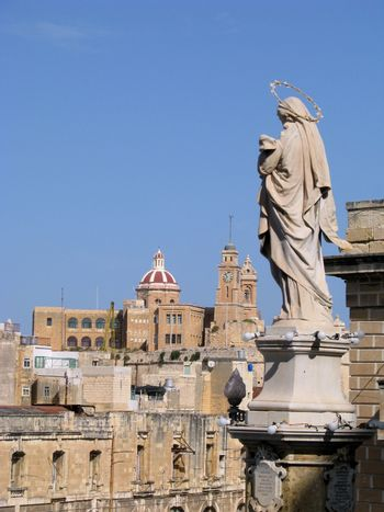 A marble statue of The Immaculate Conception in Cospicua - Malta with the church of Senglea in the background.