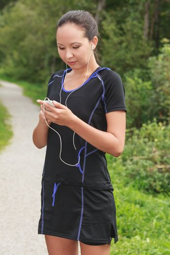 Fit young jogger adjusting the music on her mp3