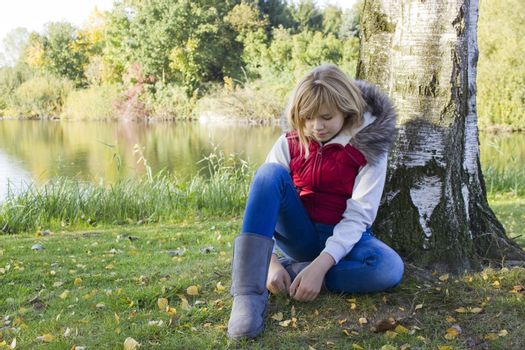 a little girl sitting under tree in autumn park by the lake