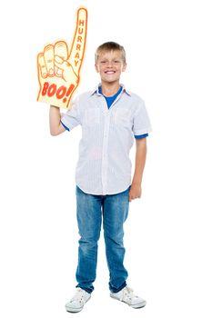 Young boy wearing a large foam hand