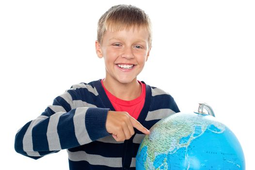 Cute little boy pointing out a continent on the globe
