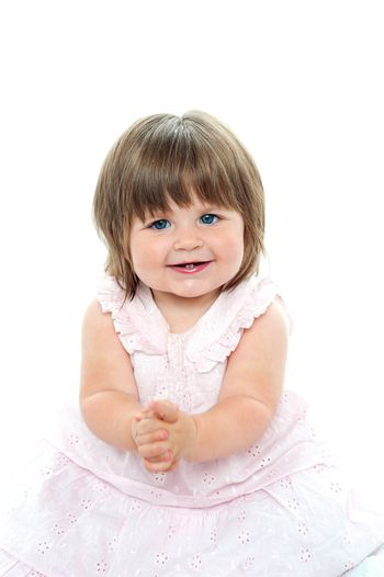 Cheerful baby girl in pink frock