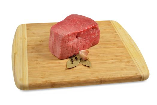 Piece of raw beef on a wooden board, decorated with garlic and bay leaves.