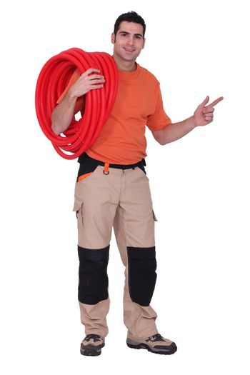 Plumber with coiled pipe pointing