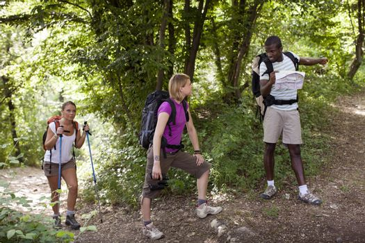 group of man and women during hiking excursion in woods, with woman looking at map and finding direction. Full length