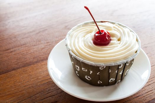 Cupcake with red cherry on white plate