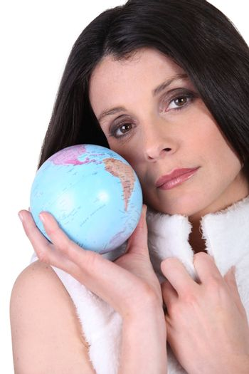 Woman in a furry gilet holding a globe