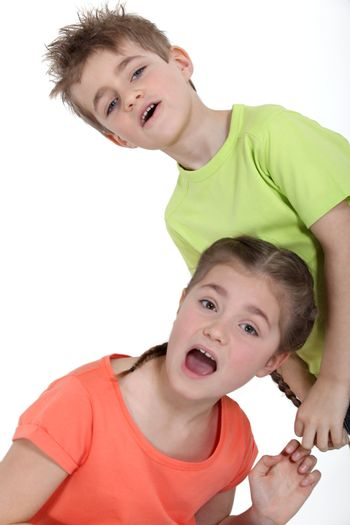 Young boy pulling his sister's braid