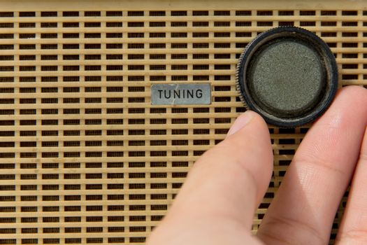hand with tuner radio knob