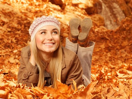 Woman lay down on autumnal foliage