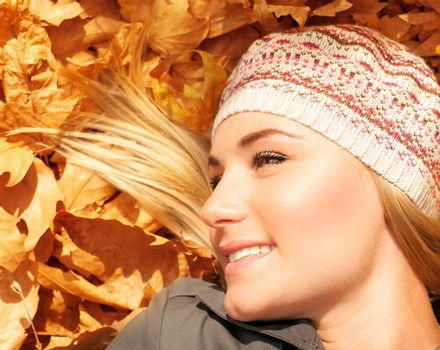 Cute blonde laying down on tree leaves