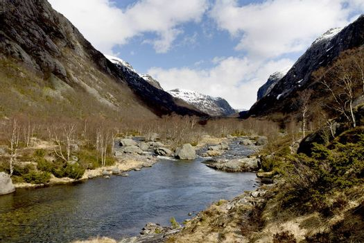 rural valley with riveron norway - cloudy sky