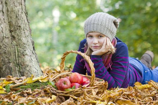 young girl with basket of apples in autumn garden