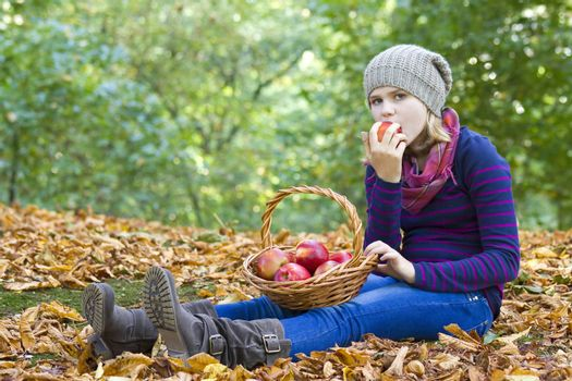 young girl eating red apple in autumn garden
