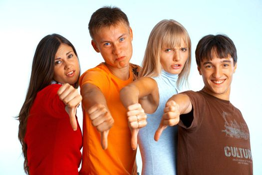 Four young people on white background and giving the thumbs-down sign.