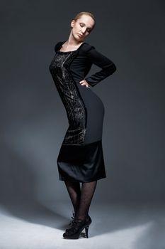 Full length portrait of beautiful model in black retro dress, posing.