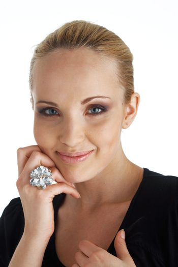 Close-up portrait of a blond model, smiling and holding a hand under her cheek.