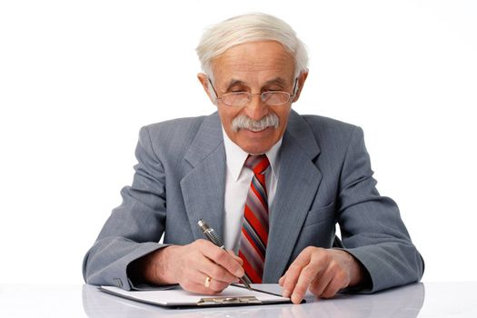 Portrait of an elder businessman writing something in the document over white.