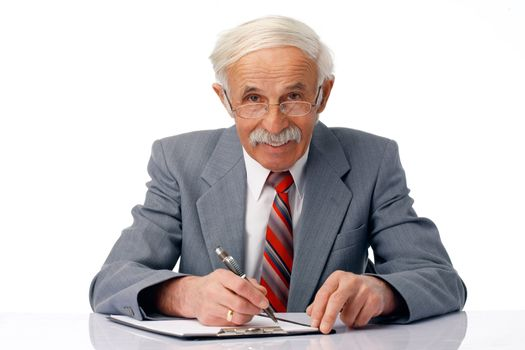 Portrait of an elder smiling man writing something and looking at you.